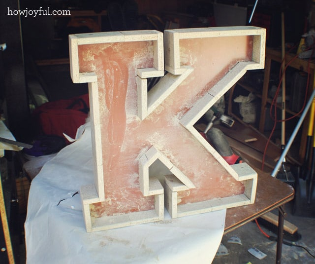 sanding the oversize letter marquee